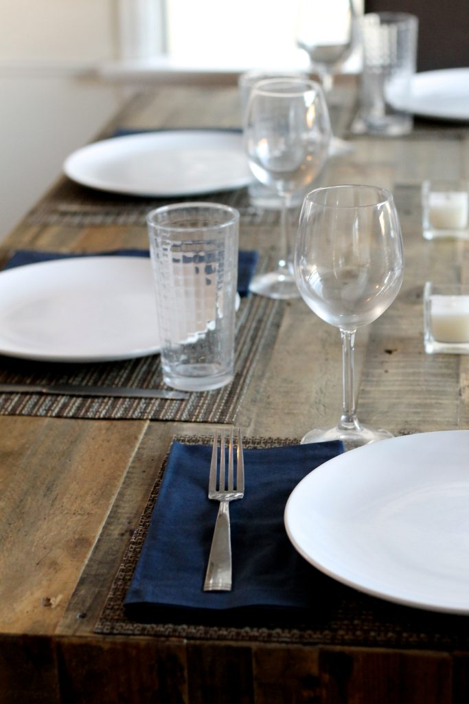 West Elm Emmerson Table set with glasses, candles, navy blue napkins | www.littlechefbigappetite.com