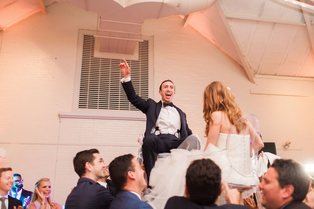 Bride and Groom in Chairs During Hora | www.littlechefbigappetite.com